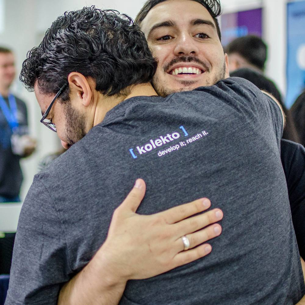 image of two kolekto employees hugging amicably at a company meeting and depicting the kolekto logo on their backs
