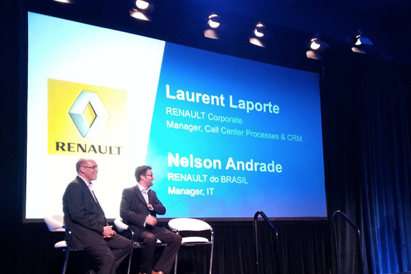 image of two people sitting in front of a big screen with the Renault logo